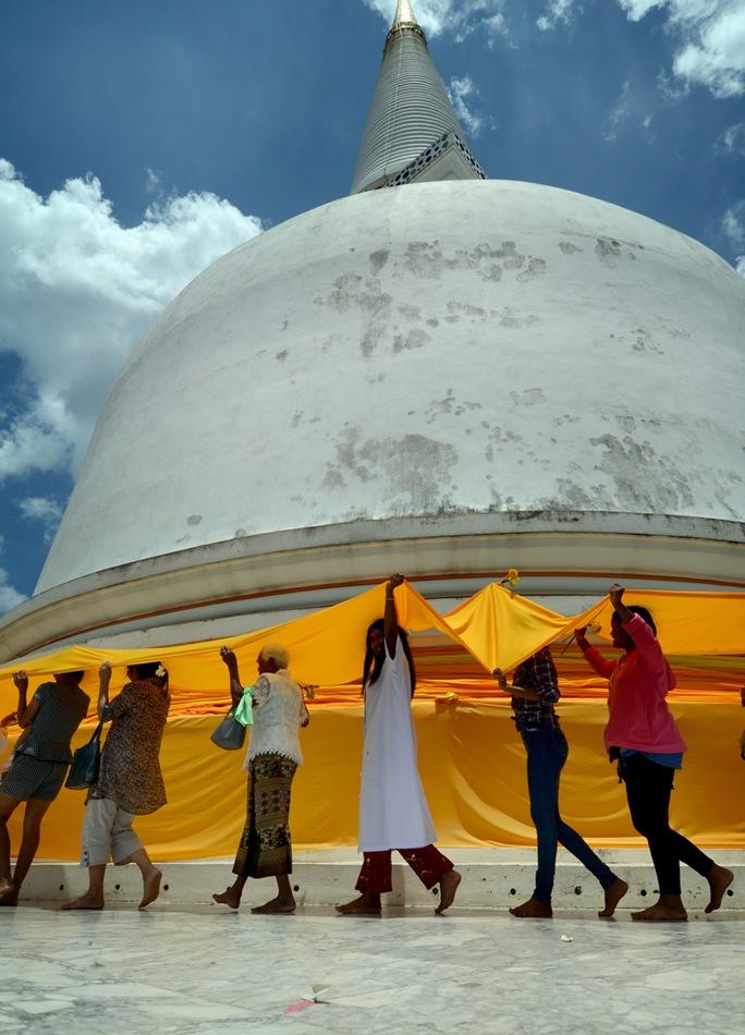 Peregrinos dan vueltas a la estupa sagrada de Wat Phra Mahathat