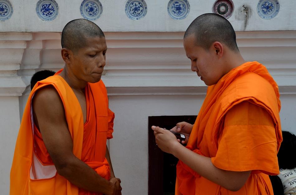 Dos monjes budistas whasappean ante la estupa sagrada de Wat Phra Mahathat.